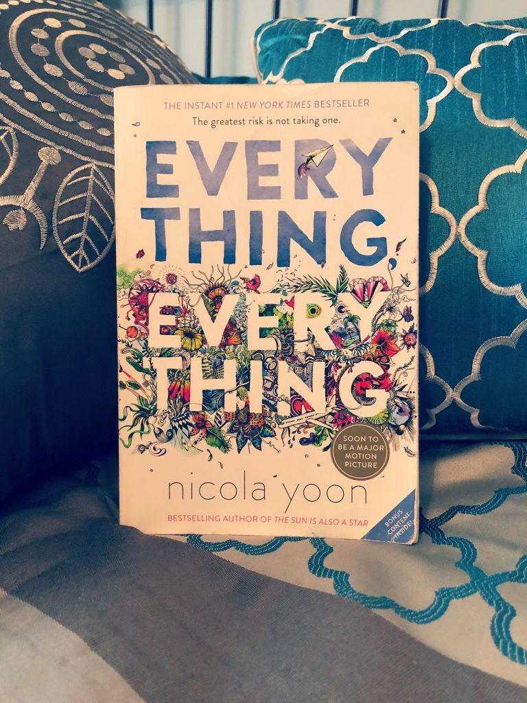 Novel Everything, Everything by Nicola Yoon propped up on a blue pillow