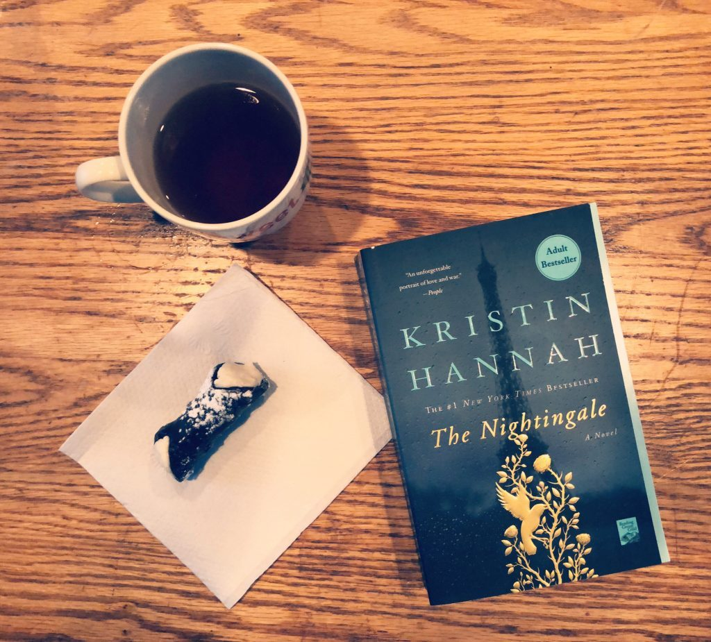 Novel The Nightingale by Kristin Hannah sitting on a table with coffee and a pastry