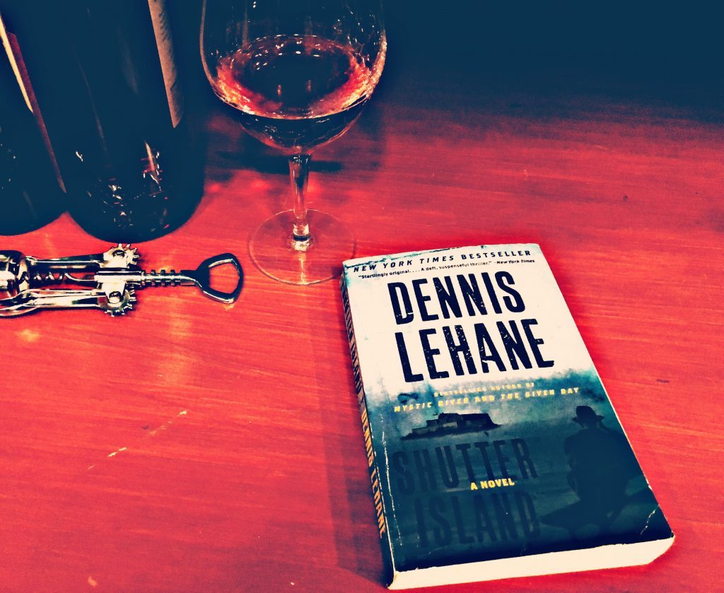 Novel Shutter island by Dennis Lehane on a bar with a glass of wine
