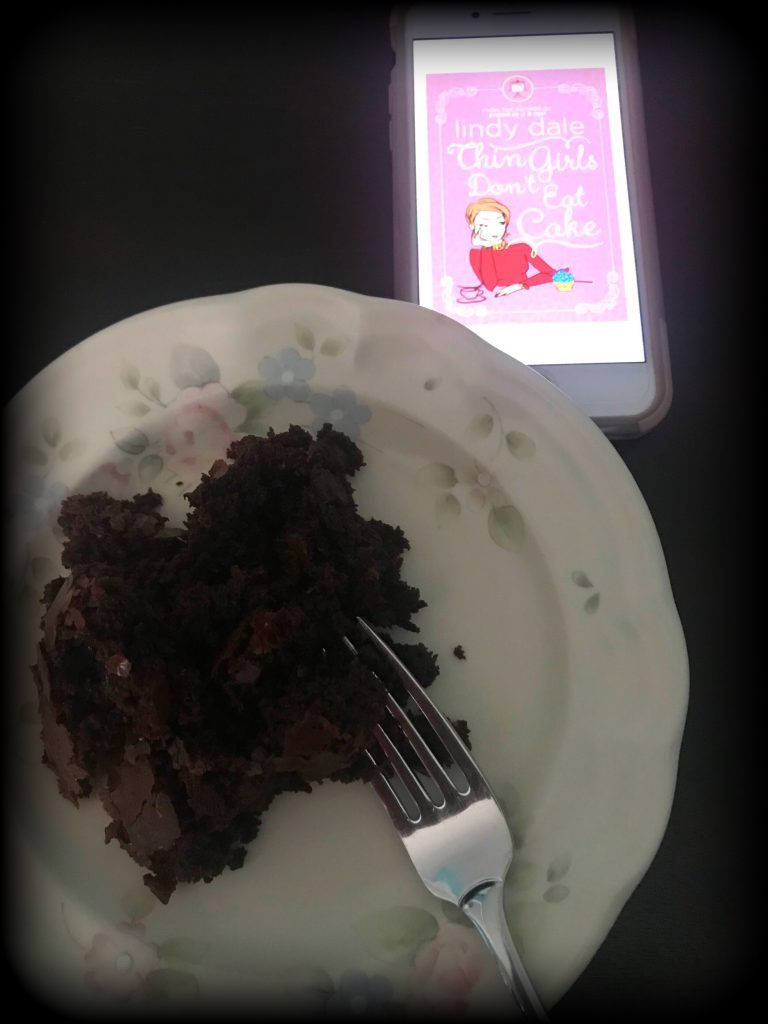 Kindle version of novel Thin Girls Don't Eat Cake next to a piece of cake