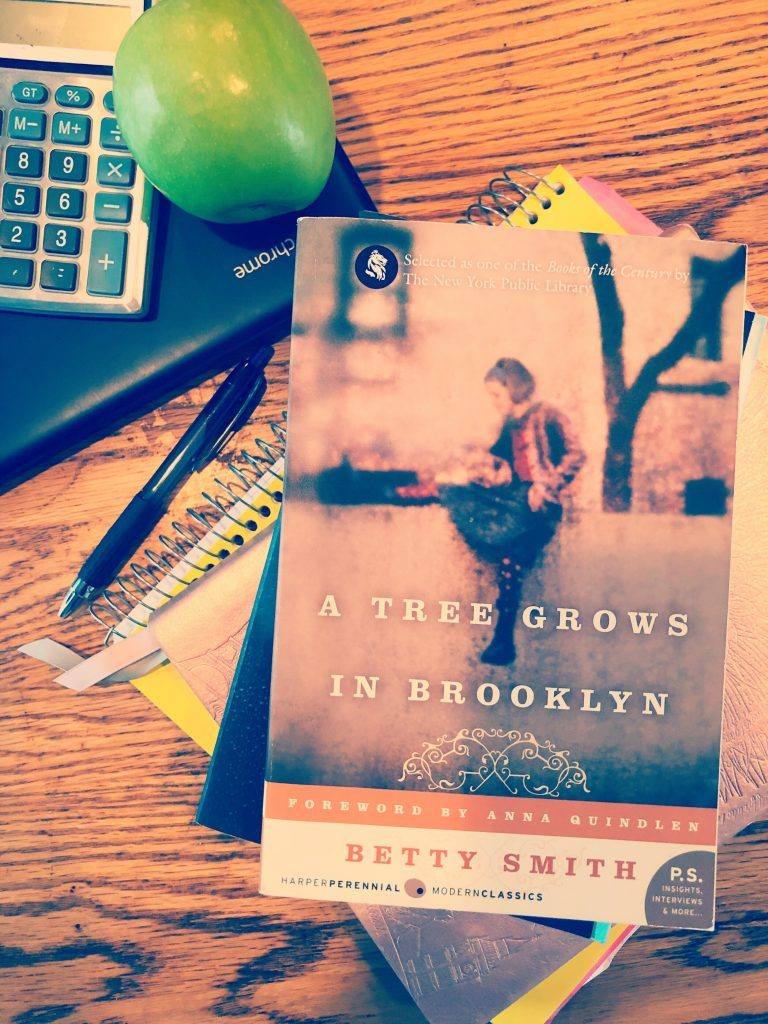 Novel A Tree Grows in Brooklyn on a table with school books and an apple