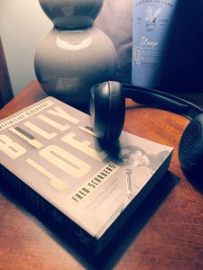 Novel about Billy Joel by Fred Schruers lying on a nightstand with headphones